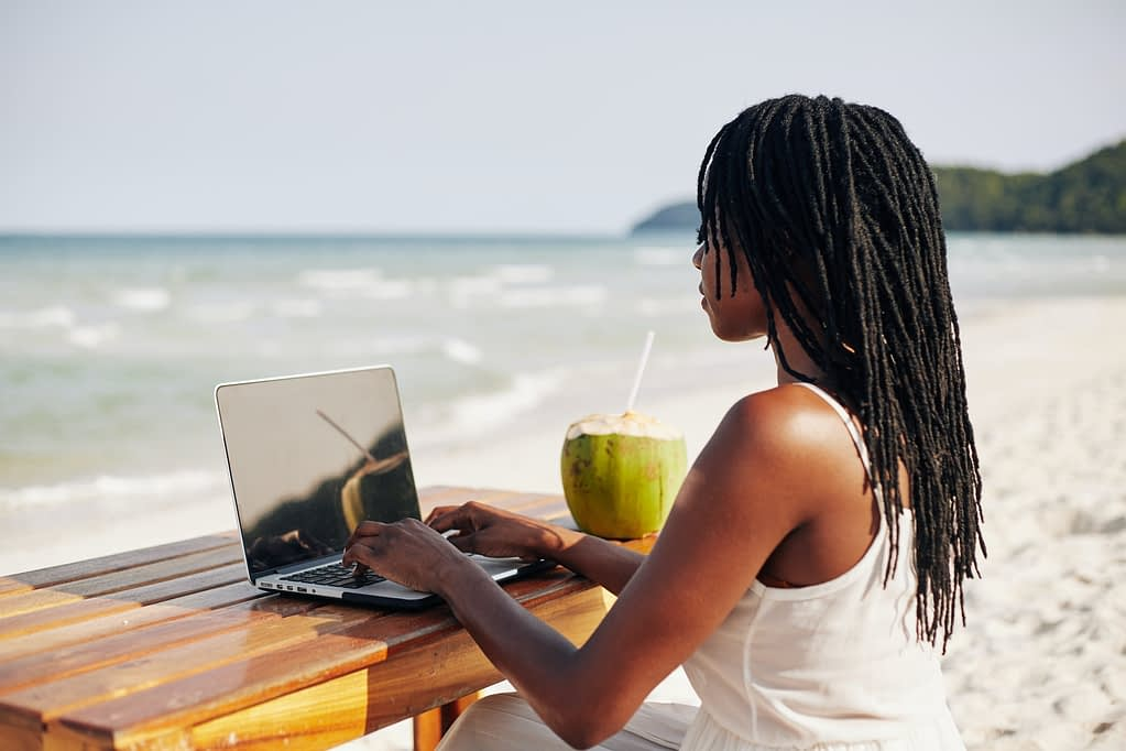 Young woman working on computer on beach
